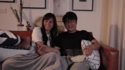 laughing asian chinese couple watching movies while eating popcorn at home