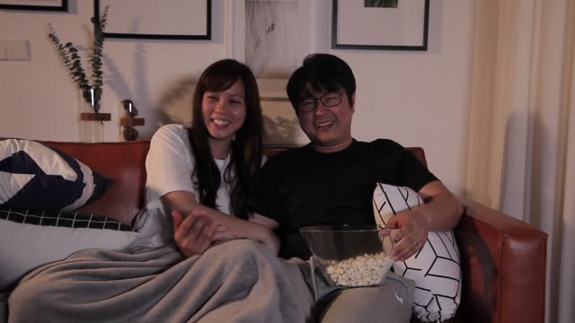 laughing asian chinese couple watching movies while eating popcorn at home - husband stock videos & royalty-free footage
