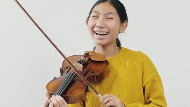黄色のセーターを着て笑うアジアの女子高生は、灰色の背景、ライフスタイルのコンセプトでバイオリンを演奏することを学びます。 - バイオリン奏者点の映像素材/bロール