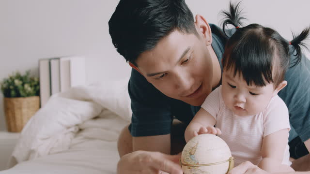 laughing baby with father learning the globe. - innocence stock videos & royalty-free footage