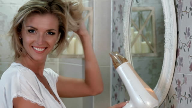 laughing beautiful woman dries her hair with hairdryer - beautiful woman stock videos & royalty-free footage