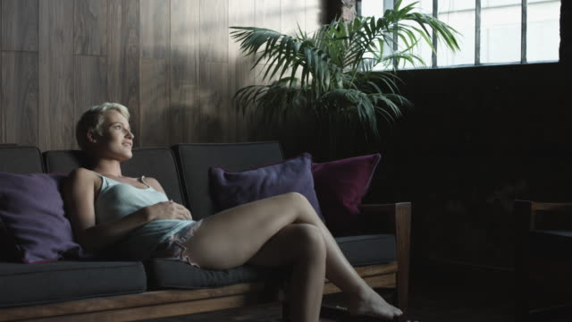 laughing blonde woman on couch, medium shot - kamisol stock-videos und b-roll-filmmaterial