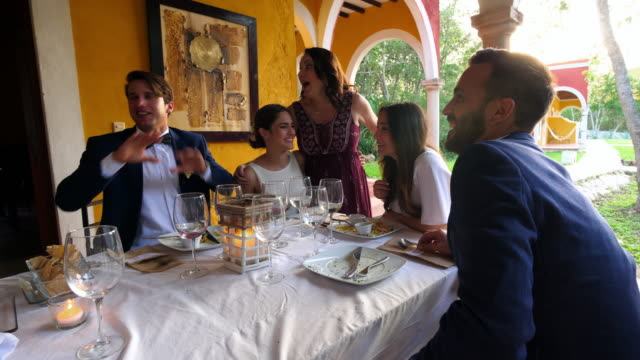 MS Laughing bride and groom enjoying dinner with wedding guests during outdoor wedding reception