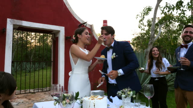 ms laughing bride feeding cake to groom during outdoor wedding reception - wife sharing stock-videos und b-roll-filmmaterial