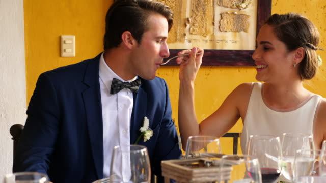 vídeos de stock, filmes e b-roll de ms laughing bride feeding groom at outdoor wedding reception dinner - garfo