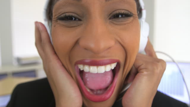 laughing business woman listening to music at work - lingua umana video stock e b–roll