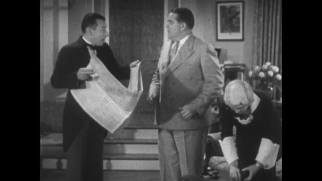 1934 laughing butler reads newspaper before being questioned by stern boss - crumpled paper stock videos and b-roll footage