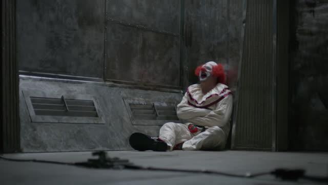 Laughing clown sitting on floor of mental asylum wearing straight jacket / Cedar Hills, Utah, United States