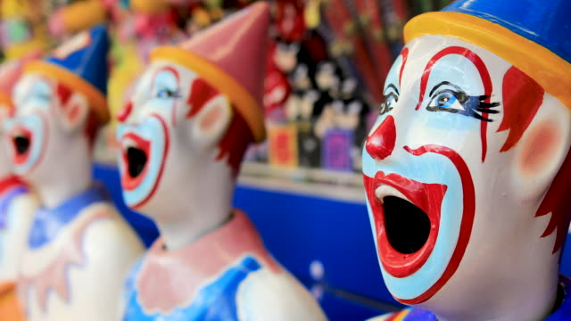 laughing clowns in sideshow alley at local fair - game show stock videos & royalty-free footage
