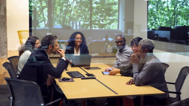 ms td laughing colleagues meeting with clients in office conference room - arbeitsstätten stock-videos und b-roll-filmmaterial