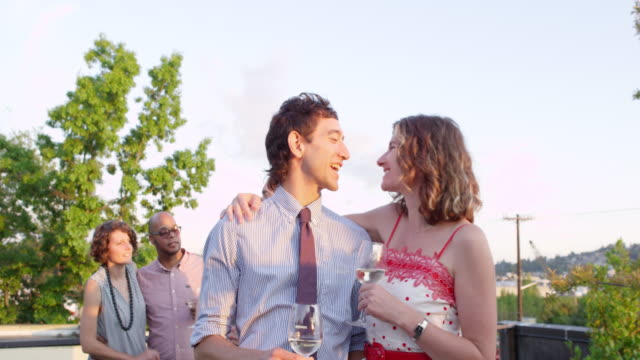 MS Laughing couple kissing and drinking wine on rooftop deck at sunset with friends in background