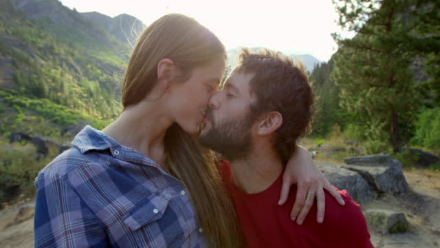 ms laughing couple kissing at mountain lookout - wilderness stock videos & royalty-free footage