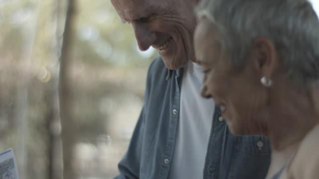 vidéos et rushes de laughing elderly couple look at map, close up - retraite