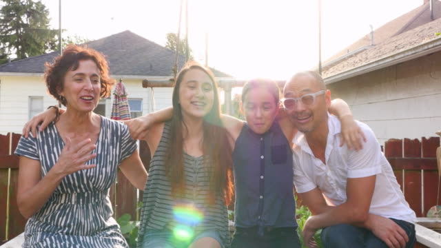 ms zi laughing family embracing in backyard garden of home on summer evening - gruppo multietnico video stock e b–roll