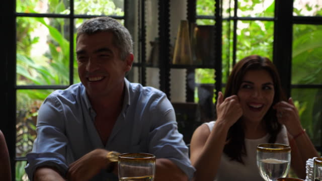 vídeos de stock e filmes b-roll de ms laughing family gathered for birthday dinner - 50 anos