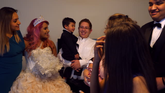 MS Laughing family members in living room with young woman dressed in quinceanera gown