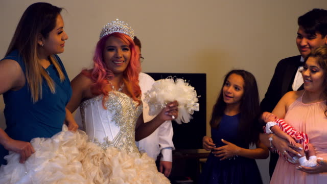 ms laughing family members in living room with young woman dressed in quinceanera gown - 14 15 anni video stock e b–roll