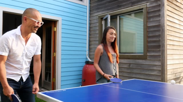 ms laughing father and daughter playing ping pong in backyard of home on summer evening - modern manhood stock videos & royalty-free footage