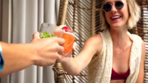 ms laughing female couple toasting drinks while relaxing in hanging chairs - alcohol drink stock videos & royalty-free footage