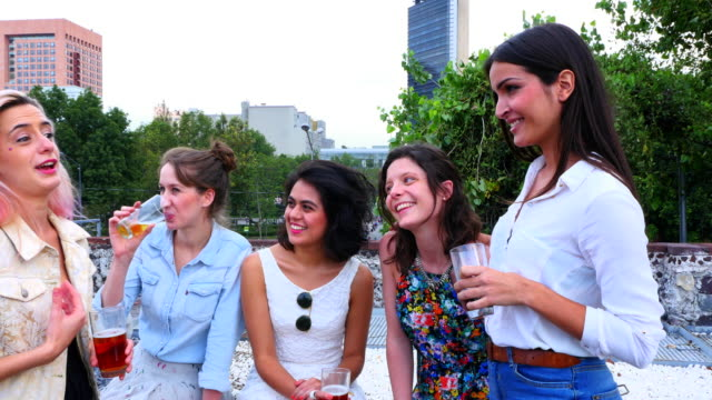MS PAN Laughing female friends having drinks together during party on rooftop deck