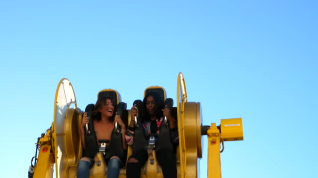 stockvideo's en b-roll-footage met ts laughing female friends riding ride at amusement park - attractiepark