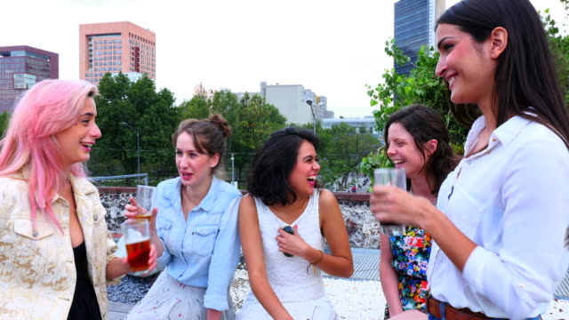 MS SWISH PAN Laughing female friends talking and having drinks together on rooftop deck