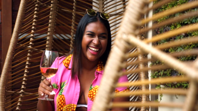 ms laughing female friends toasting drinks while relaxing in hanging chairs - indulgenza video stock e b–roll