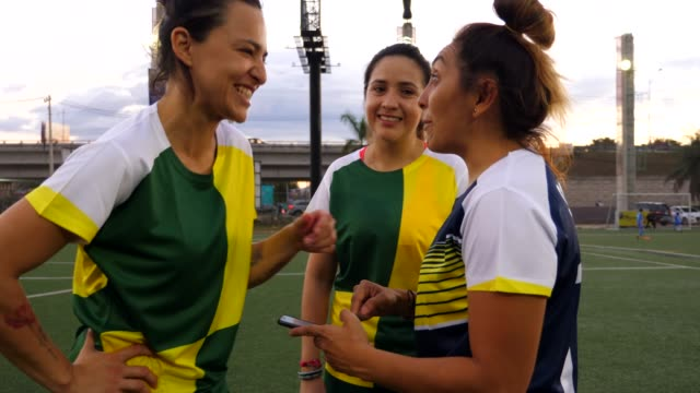 MS Laughing female soccer players looking at smart phone after game