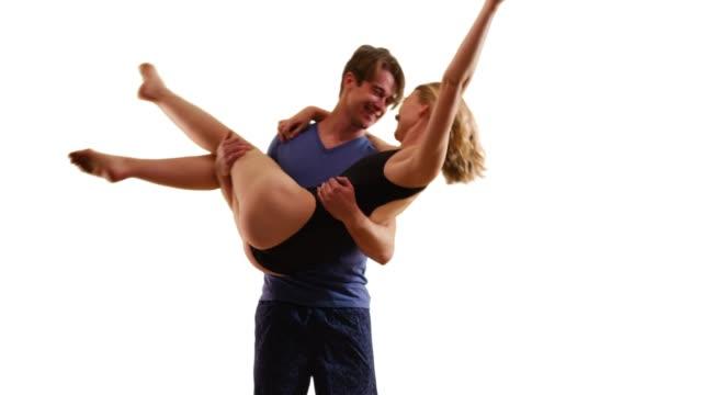 vídeos y material grabado en eventos de stock de laughing female wearing bathing suit being carried by boyfriend in studio - bañador de natación