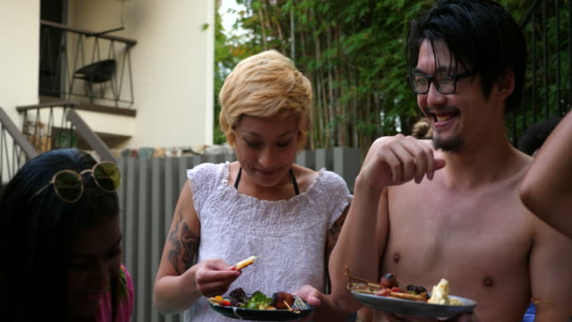 PAN Laughing friends enjoying appetizers during pool party
