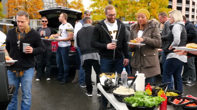 ms zo laughing friends hanging out during tailgating party in stadium parking lot - community stock videos & royalty-free footage