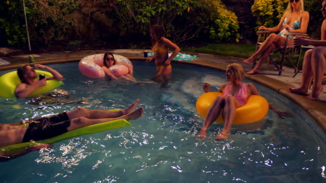 PAN Laughing friends hanging out together in backyard pool during party on summer evening