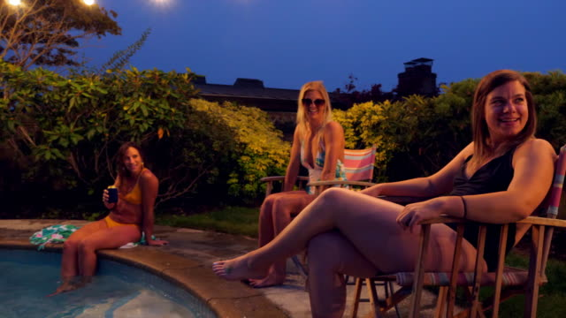 MS ZI Laughing friends hanging out together in backyard pool during party on summer evening