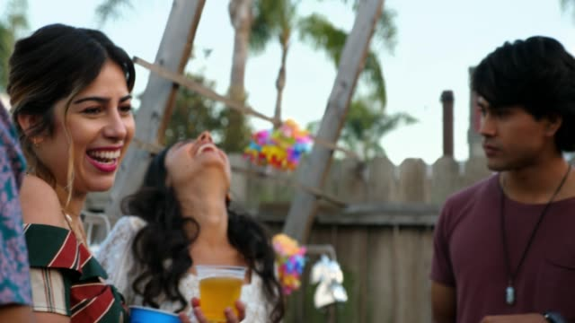 ms laughing friends in discussion during backyard party on summer evening - etnia latino americana video stock e b–roll