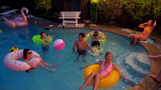 MS Laughing friends in discussion while floating in pool on a summer evening