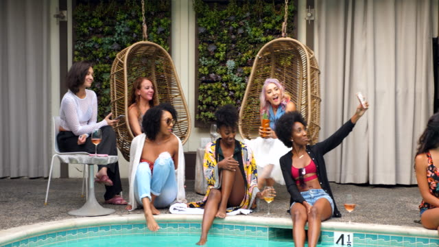stockvideo's en b-roll-footage met ms laughing friends in discussion while taking selfie by pool during party - zwembadrand