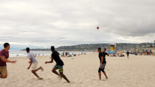 ms laughing friends playing touch football game on beach - touch football video stock e b–roll