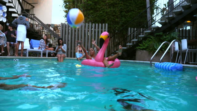 ms laughing friends playing with inflatable beach ball during hotel pool party - ビーチボール点の映像素材/bロール