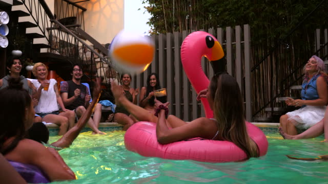ms laughing friends playing with inflatable beach ball during hotel pool party - poolside stock videos & royalty-free footage