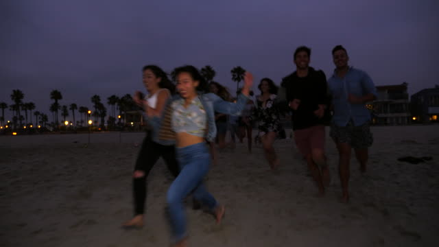 ts laughing friends running into ocean during beach party on summer evening - 避ける点の映像素材/bロール