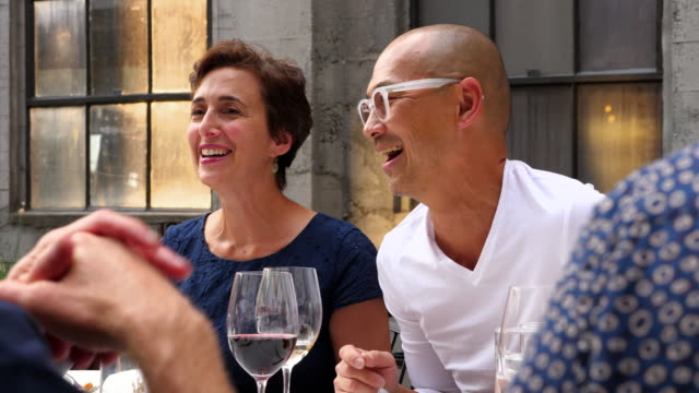 ms laughing friends sharing celebration dinner on restaurant patio - wine glass stock videos and b-roll footage