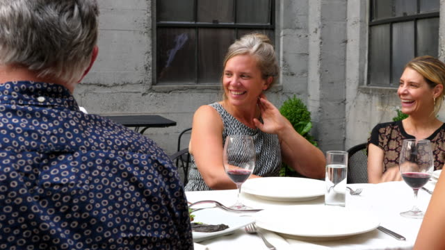 PAN Laughing friends sharing celebration meal on outdoor patio