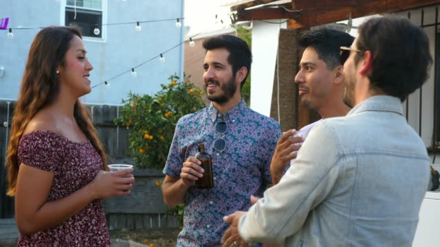 ms laughing friends sharing drinks during backyard party on summer evening - social gathering stock videos & royalty-free footage
