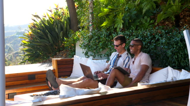 ms laughing gay couple looking at laptop together while relaxing in backyard - only mid adult men stock videos & royalty-free footage