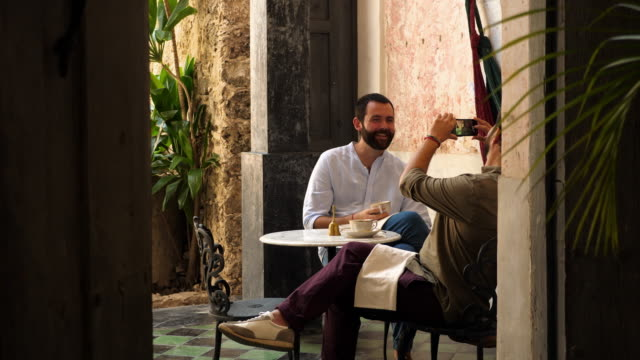 MS Laughing gay man taking picture of partner with smartphone while sitting in outdoor cafe during vacation