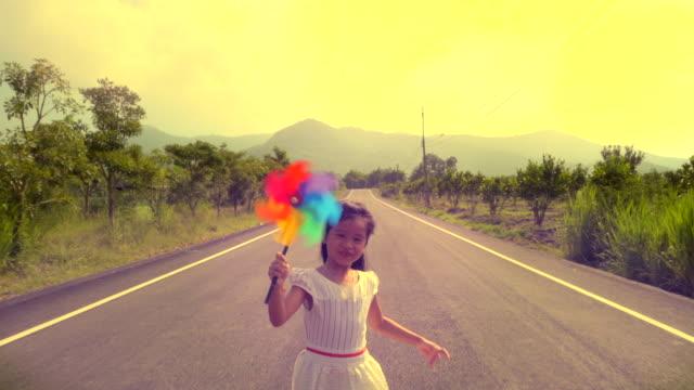 虹のピンホイールのおもちゃを持つ笑いの女の子 - おもちゃ点の映像素材/bロール