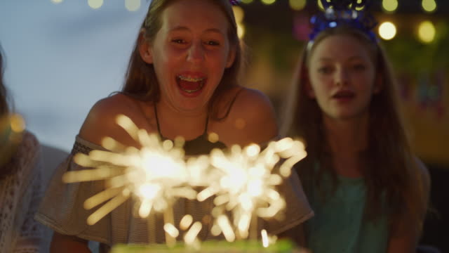 vídeos de stock e filmes b-roll de laughing girl trying to extinguish sparklers on birthday cake / cedar hills, utah, united states - 12 13 anos