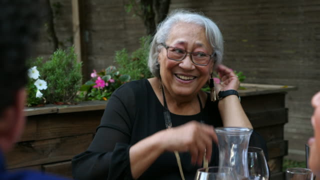 ms laughing grandmother in discussion with mature daughter during outdoor dinner party - eleganz stock-videos und b-roll-filmmaterial