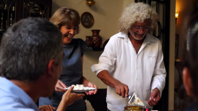 ms laughing grandmother serving birthday cake for family during birthday dinner - older woman fun stock-videos und b-roll-filmmaterial
