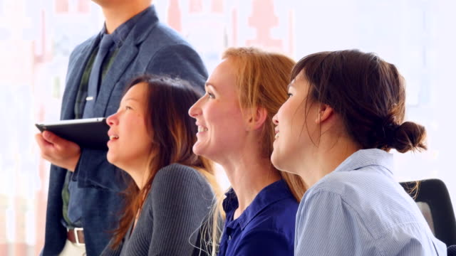 MS Laughing group of businesswomen listening to presentation in office conference room